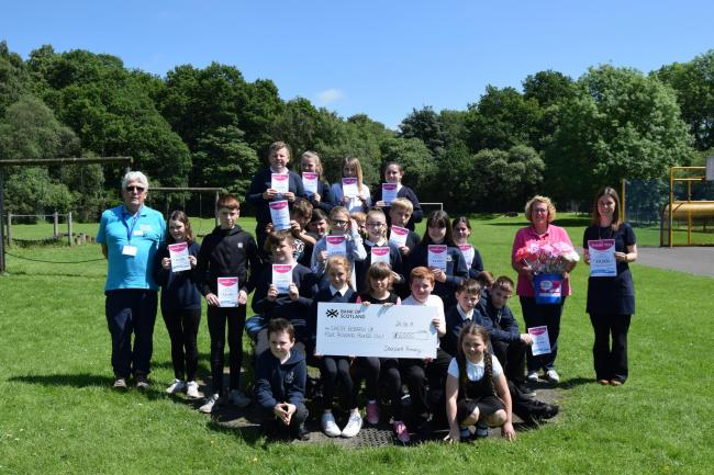 Ms Wyman's P6-7 class at Deerpark Primary with a cheque for £4,000 which was handed over to the Wee County CRUK fundraising group's Nicky and Ian Whyte