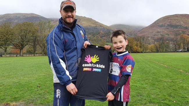 KIND HEART: Alex Croucher, who also coaches at Hillfoots RFC in Tillicoultry, with a Cash for Kids T-shirt and his son Hamish