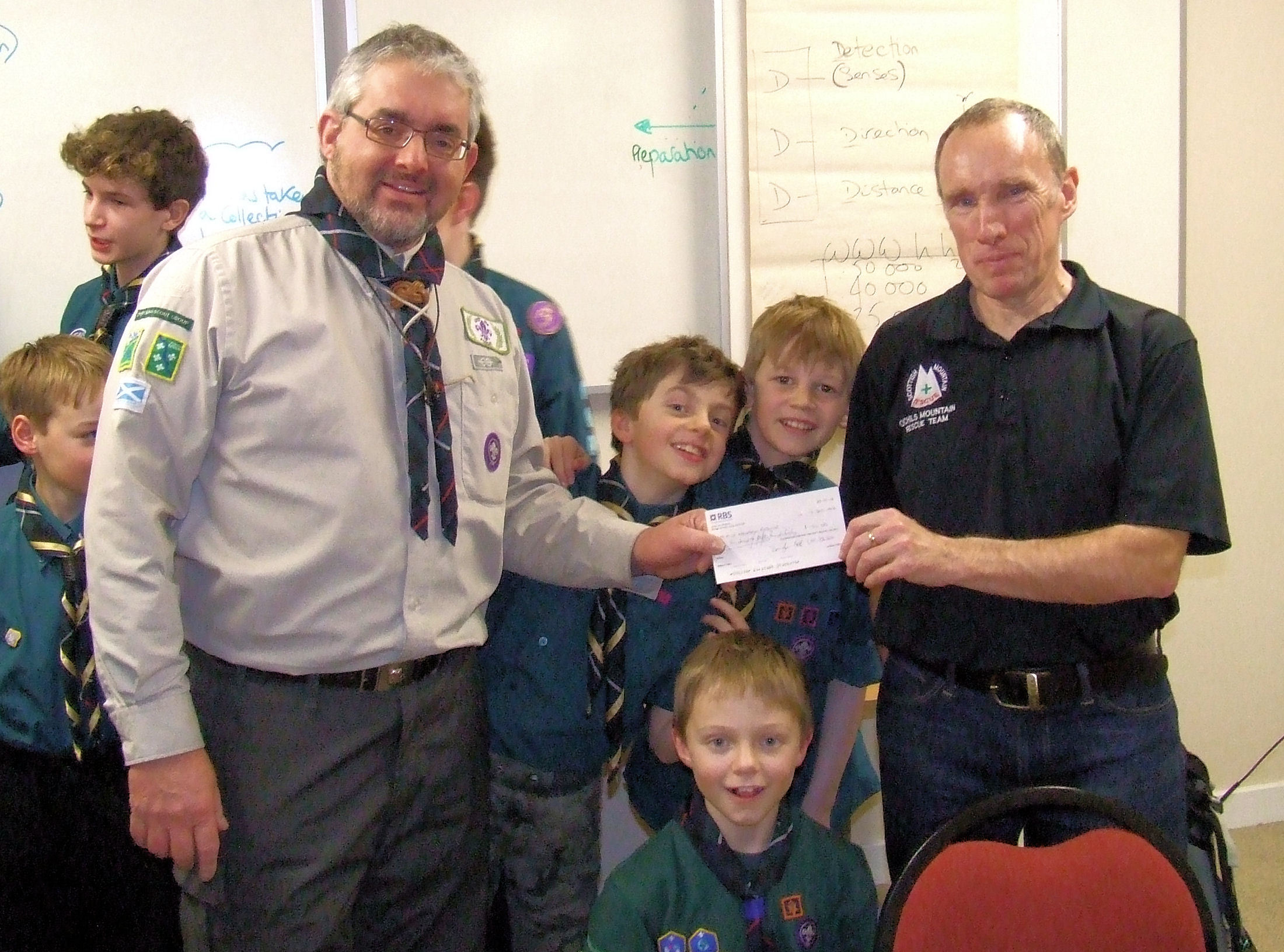 Dollar Scout Group leader Neil Schofield presents a cheque for £150 to Robert Davidson, leader of the Ochils Mountain Rescue Team